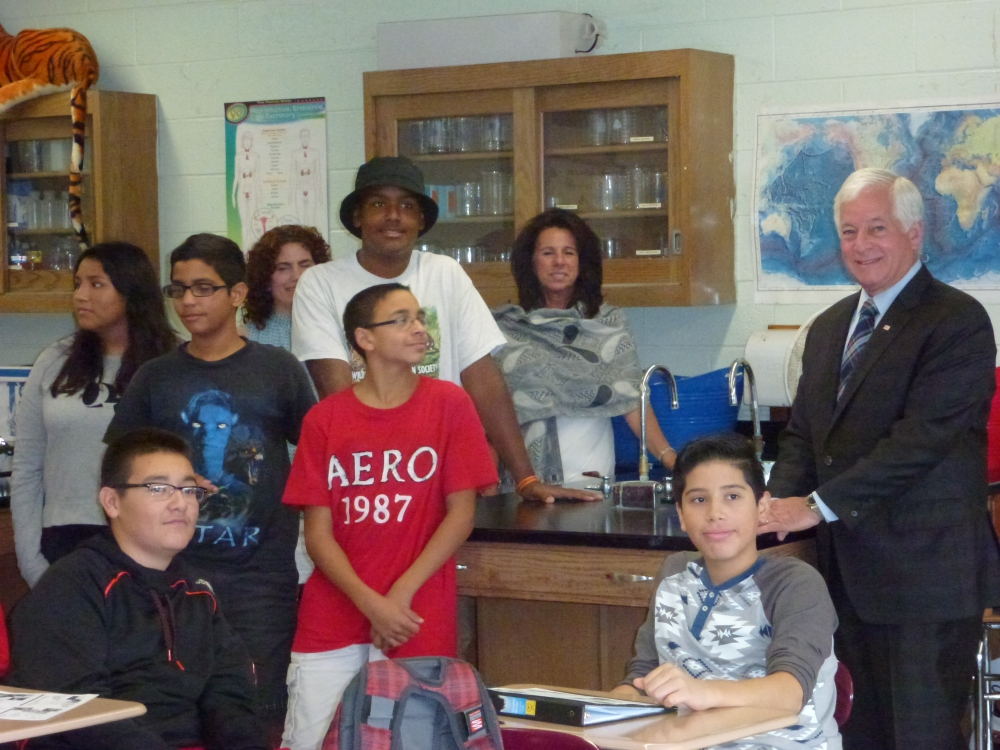 Assemblyman Charles Lavine, right, joined Glen Cove School District Superintendent of Schools Maria Rianna, rear right, science teacher Mrs. Graziosi, rear center, and students in one of the science l