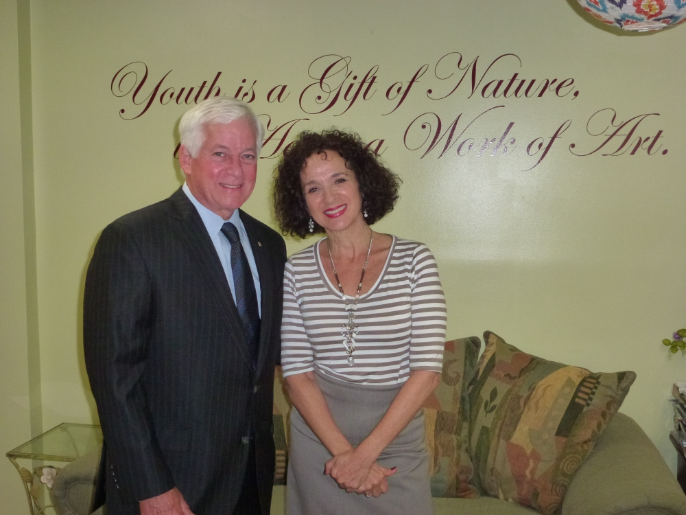 Assemblyman Charles Lavine (D-Glen Cove) and Lisa Craig, Program Director of the Glen Cove Adult Day Program, stand beneath a sign that states �Youth is a Gift of Nature, Aging is a Work of Art� durin