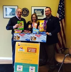 Assemblyman Dave McDonough (left) presents donations his office collected for the Long Island Cares Pet Food Drive to Elana Sissons and Michael Haynes of LI Cares.