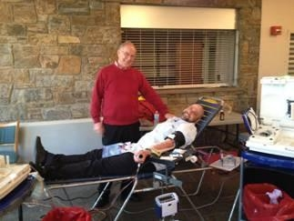 Assemblyman Dave McDonough looks on as Steven Lieberman donates blood during his blood drive.