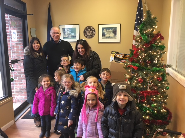 Assemblyman Dave McDonough (R,C,I-Merrick) is seen with children from the South Shore Country Day School and their teacher, Holly Kearney, who have donated toys for the past four years.