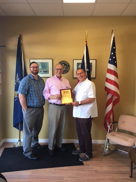 Assemblyman Dave McDonough  (R,C,I-Merrick)[center] is awarded a plaque by Long Island Cares, Inc. CEO Paule T. Pachter [right] and Chief Governmental Affairs Officer Michael W. Haynes [left] for his