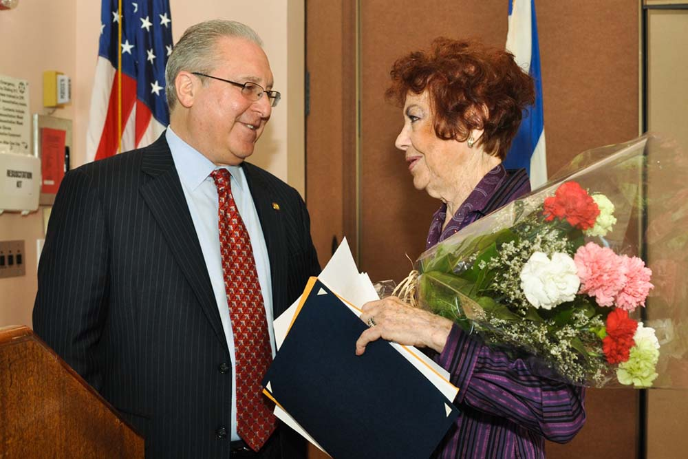 Assemblyman Steven Cymbrowitz presents flowers to late Holocaust survivor Zipora Yakuboff, the special guest speaker at his Annual Holocaust Essay, Poetry, Performance and Art Contest.