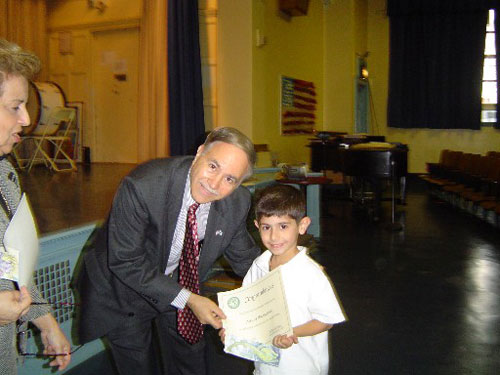 Assemblyman Colton is seen here giving a student a well-deserved reading certificate for completing the reading challenge that the Assemblyman sponsors each year.