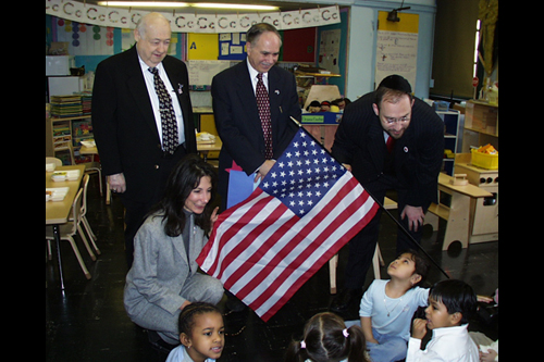 Assemblyman Colton visits P.S. 121 to deliver a flag and educate youths about its importance.