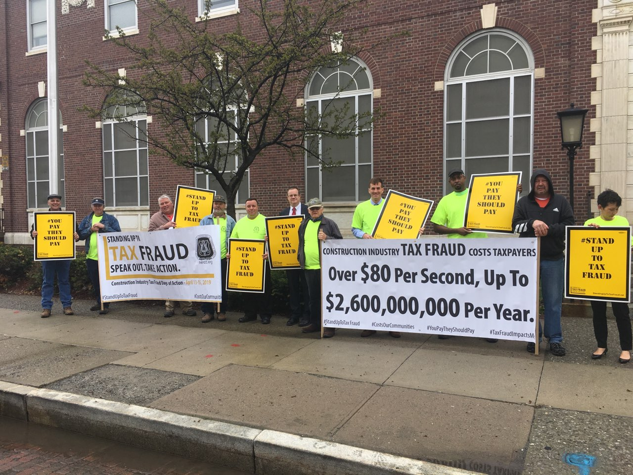 Assemblyman Karl Brabenec (R,C,I-Deerpark) [fifth from left] joins local officials and labor leaders for a rally to prevent wage theft and tax fraud in front of the Newburgh Post Office on Monday, Apr