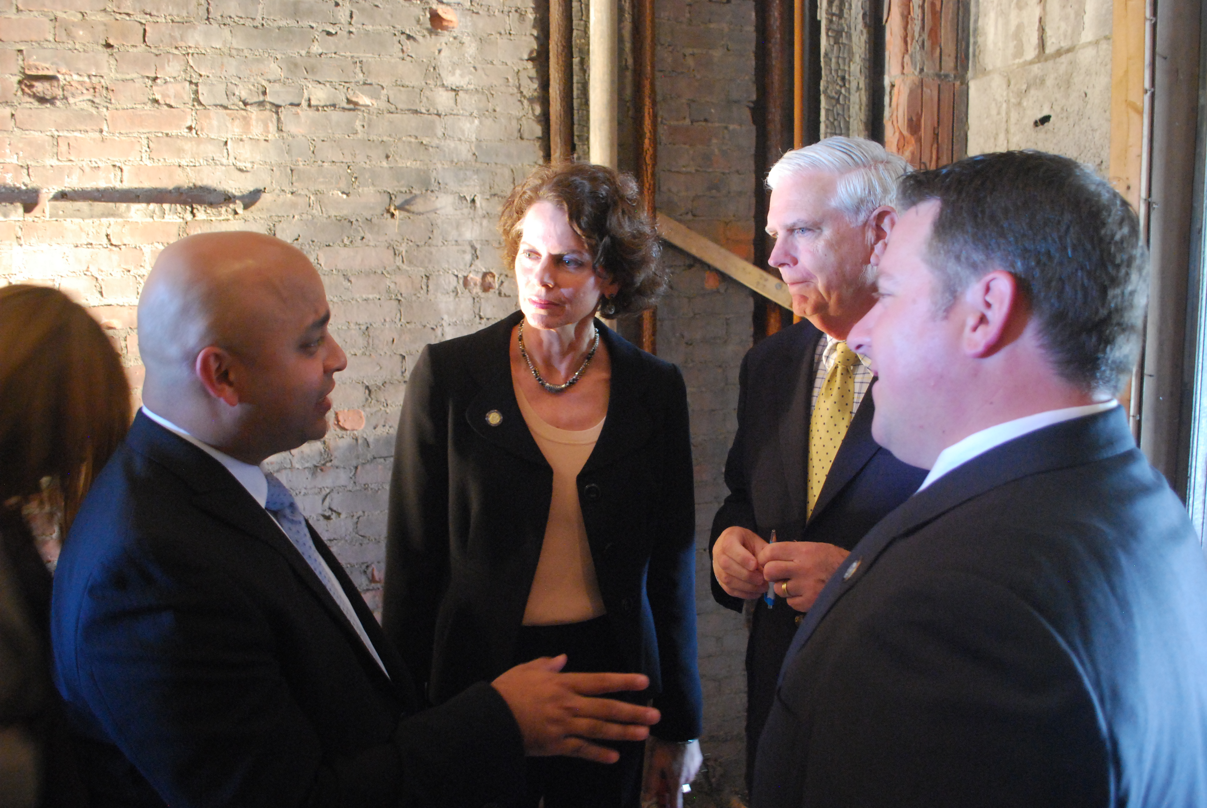 Assemblymember Patricia Fahy, along with Albany County Executive Daniel P. McCoy, listen to Aeon Nexus Executive Partner Omar Usmani talk about their new office location at 138 State Street in Downtown Albany.