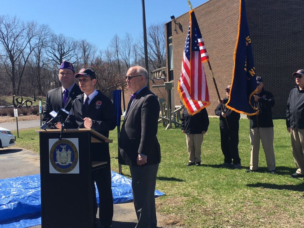 FROM LEFT: New York State Commander of the Military Order of the Purple Heart Mathew Tully, Assemblyman Angelo Santabarbara, and miSci Executive Director Mac Sudduth take the podium Friday at the Schenectady museum to unveil a Purple Heart parking space designated for veterans injured in combat. Posting the colors in the background are members of AmVets Post 35 in Rotterdam.