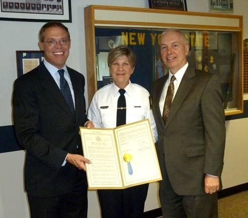 Assemblyman Will Barclay (left) and Assemblyman Bob Oaks (right) present Officer Jamie Enwright (center) with a New York State Assembly Resolution congratulating her on recently receiving the SUNY Cha