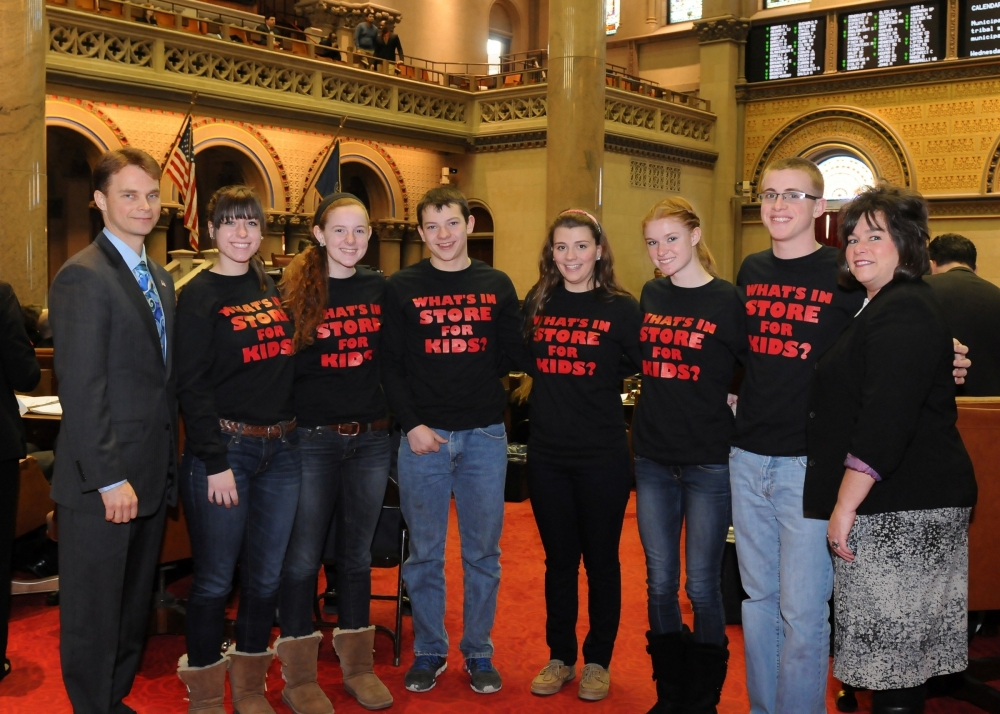 Pictured with Assemblyman Chris Friend (left) are Anna Evanek, Rachael Schweiger, Dakota Skinner, Annie Wainwright, Taylor Ayres, Dustin Sherman and Robin Baker, representatives and students from Real