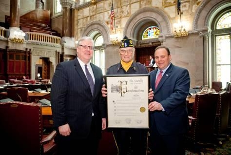 Senator Tom O'Mara (l.) and Assemblyman Phil Palmesano (r.) deliver a copy of the adopted Resolution in the New York State Senate Chamber to Philip J. Swaney, Sr., a distinguished area veteran and Sch
