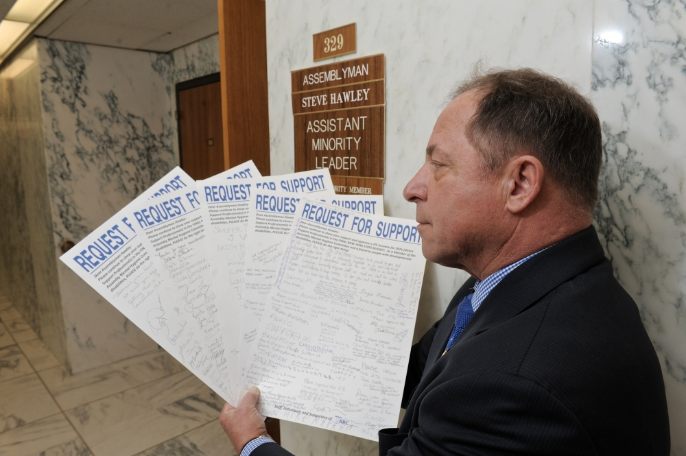 Assemblyman Steve Hawley holds signed petitions seeking improved services for people with developmental disabilities.