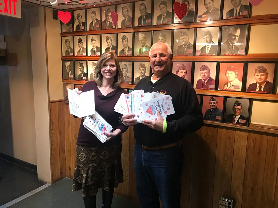 Assemblymember Monica Wallace presenting 100 Valentines for Vets cards, made by kindergarten students at Maryvale Primary School, to VFW/AMVETS Post 7275 Senior Vice Commander James Weir. Special than